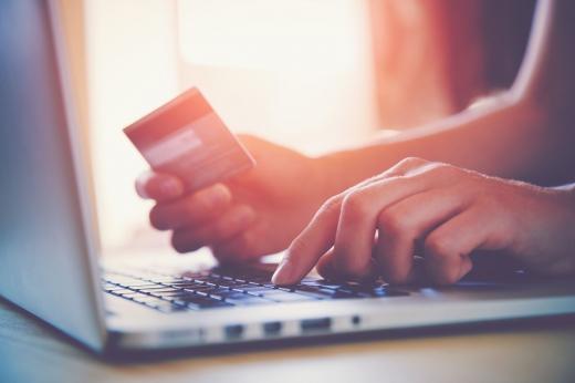 Egy férfi kezében bankkártyával, laptopot használ.