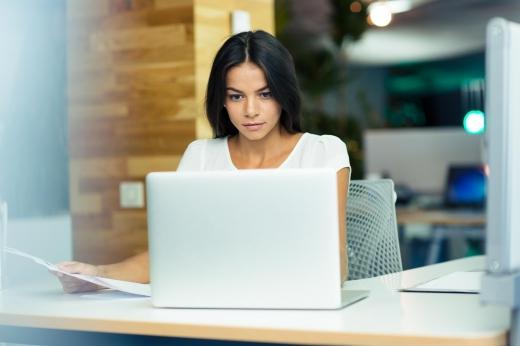 Egy fehér ruhás nő egy laptop mögött ül.