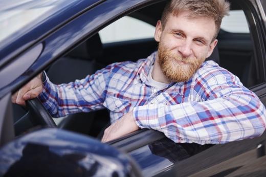 Egy szakállas férfi néz ki az autóból mosolyogva.