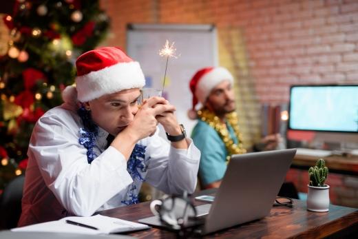 Mikulássapkás férfiak laptop előtt dolgoznak.
