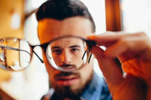 Egy férfit látunk egy szemüvegen keresztül.