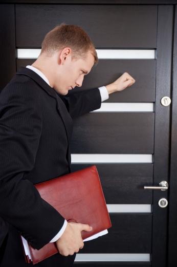 Egy piros mappás férfi egy sötét barna ajtón kopogtat.