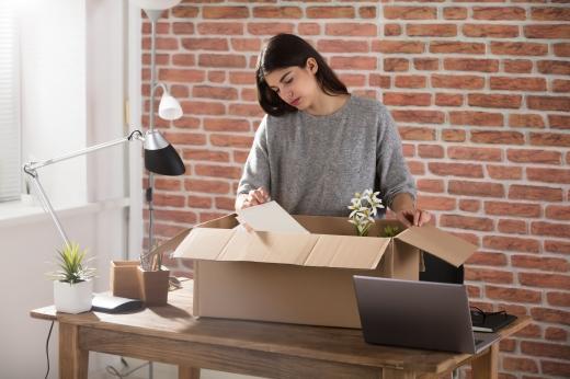 Egy sötét, hosszú hajú nő a munkahelyén egy kartondobozba pakolja a dolgait.