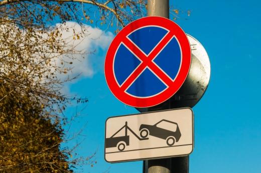 Egy megállni tilos tábla, alatta egy elszállítjuk az autóját tábla.