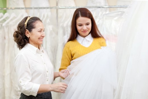 Egy sárga ruhás nő, kezében fog egy esküvői ruhát és egy fehér ruhás nőnek mutatja.