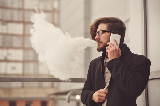 Egy férfi telefonál és közben cigifüstöt fúj ki a szájából.