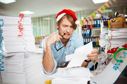 Egy mikulás sapkás férfi, papír teli asztalánál, egy papírt néz, közben a szemüvegét rágja.