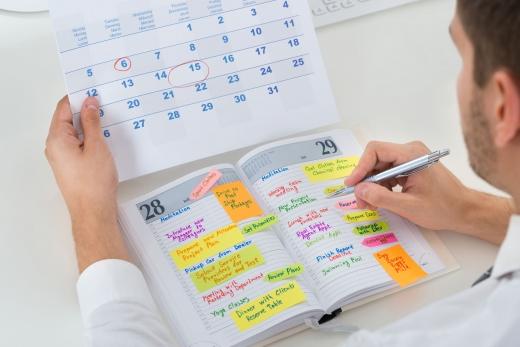 Egy férfi a naptárából a határidőnaplójába ír át programokat.
