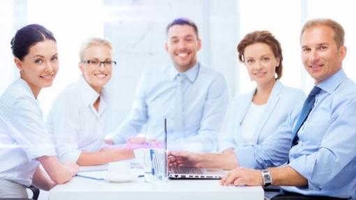Egy asztalnál ülnek fehér és kék ingeben férfiak, és egy hölgy blézerben