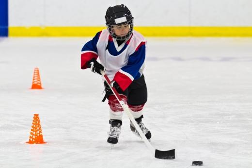 Egy jégkorongos fiú az ütővel vezet egy pakkot.
