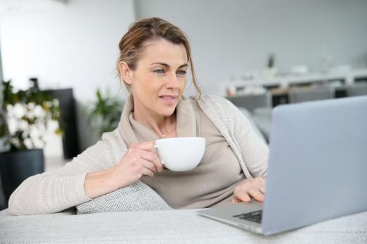 Egy nő a laptop mögött, kávéscsészével a kezében.