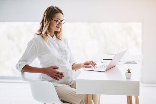 Egy fehér ruhás terhes nő egy asztalnál ül és laptopot használ.