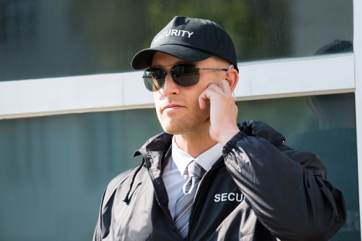 Egy napszemüveges biztonsági őr, a kezével a fülében lévő fülhallgatót tartja.