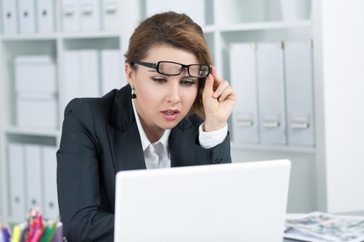 Egy nő a szemüvegét felemelve néz egy laptopot.