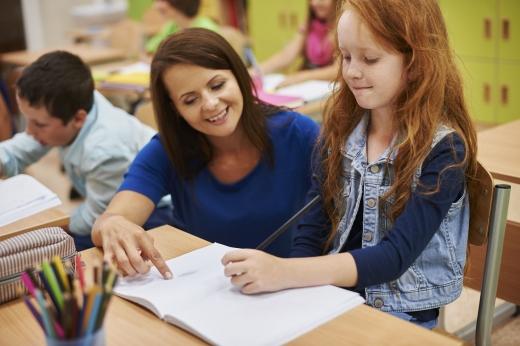 Egy nő segít egy vörös hajú kislánynak egy könyvbe rajzolni.