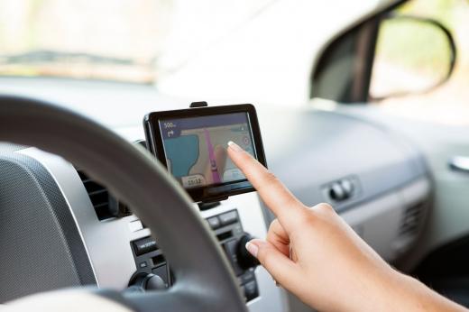 Egy nő a kocsiban az ujjával beállítja a GPS-t.