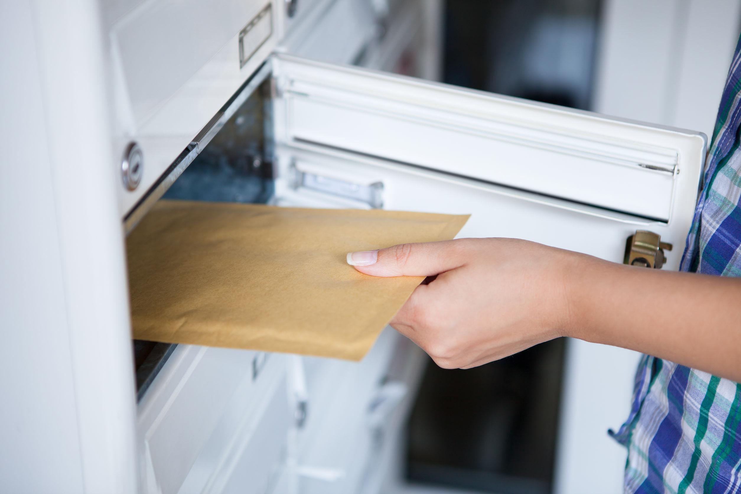 Női kéz a postaládából levelet vesz ki.