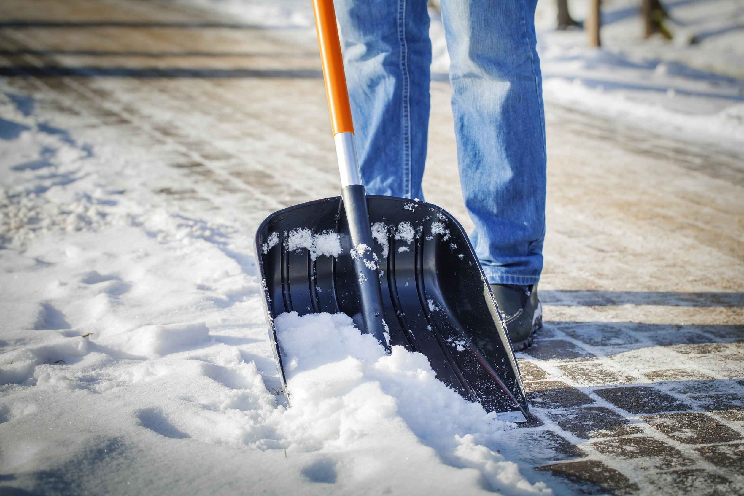 Egy ember havat lapátol.