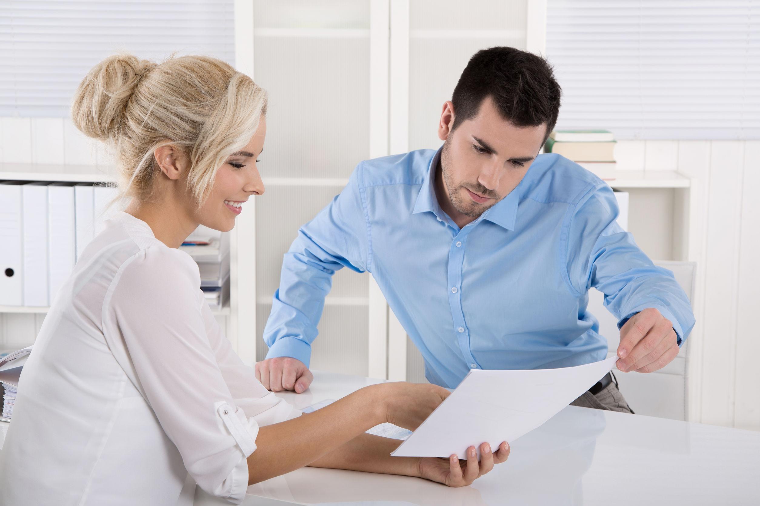 Egy fehér ruhás szőke nő, egy szerződést mutat egy kék inges férfinak.