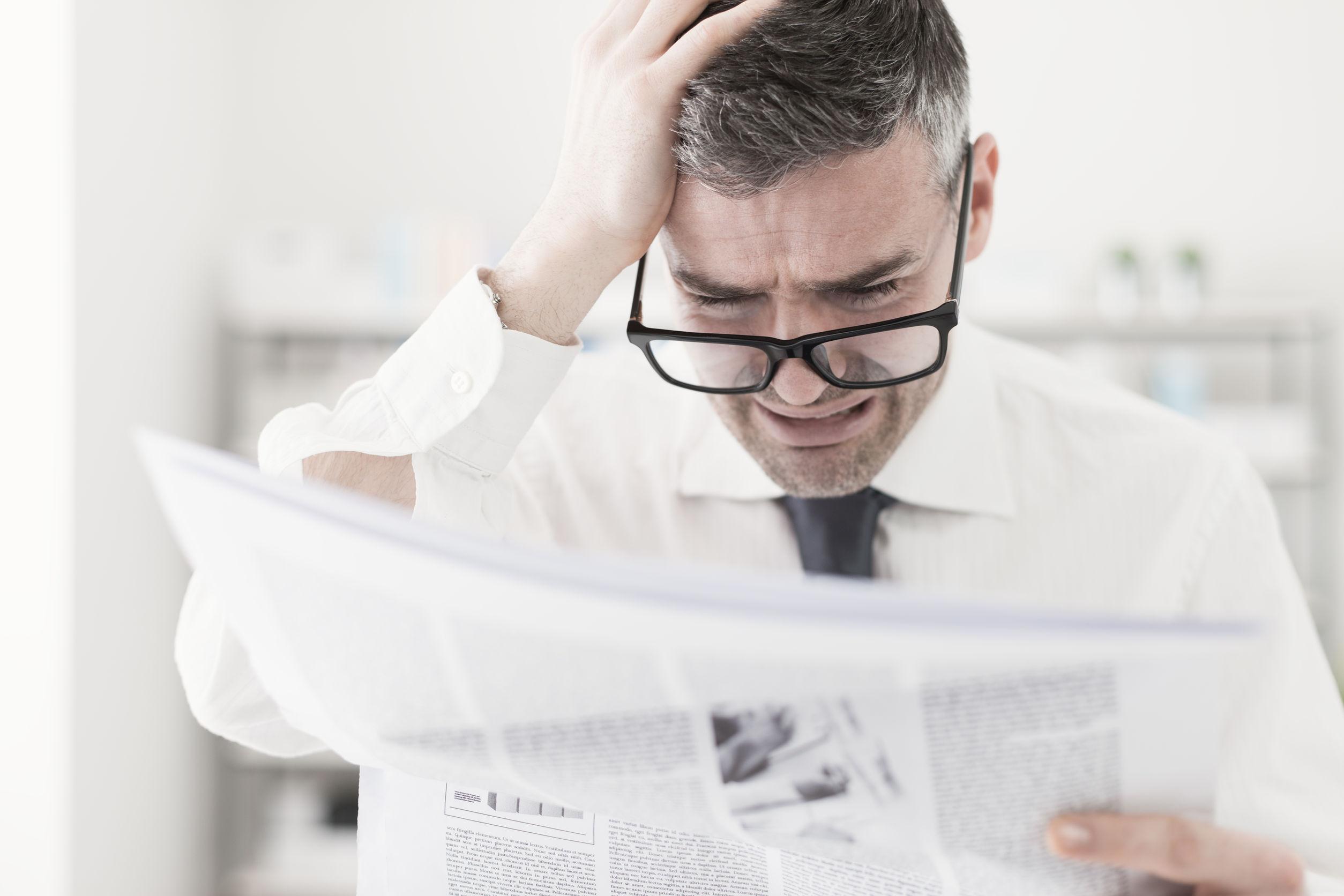 Szomorú ember újságot olvas.