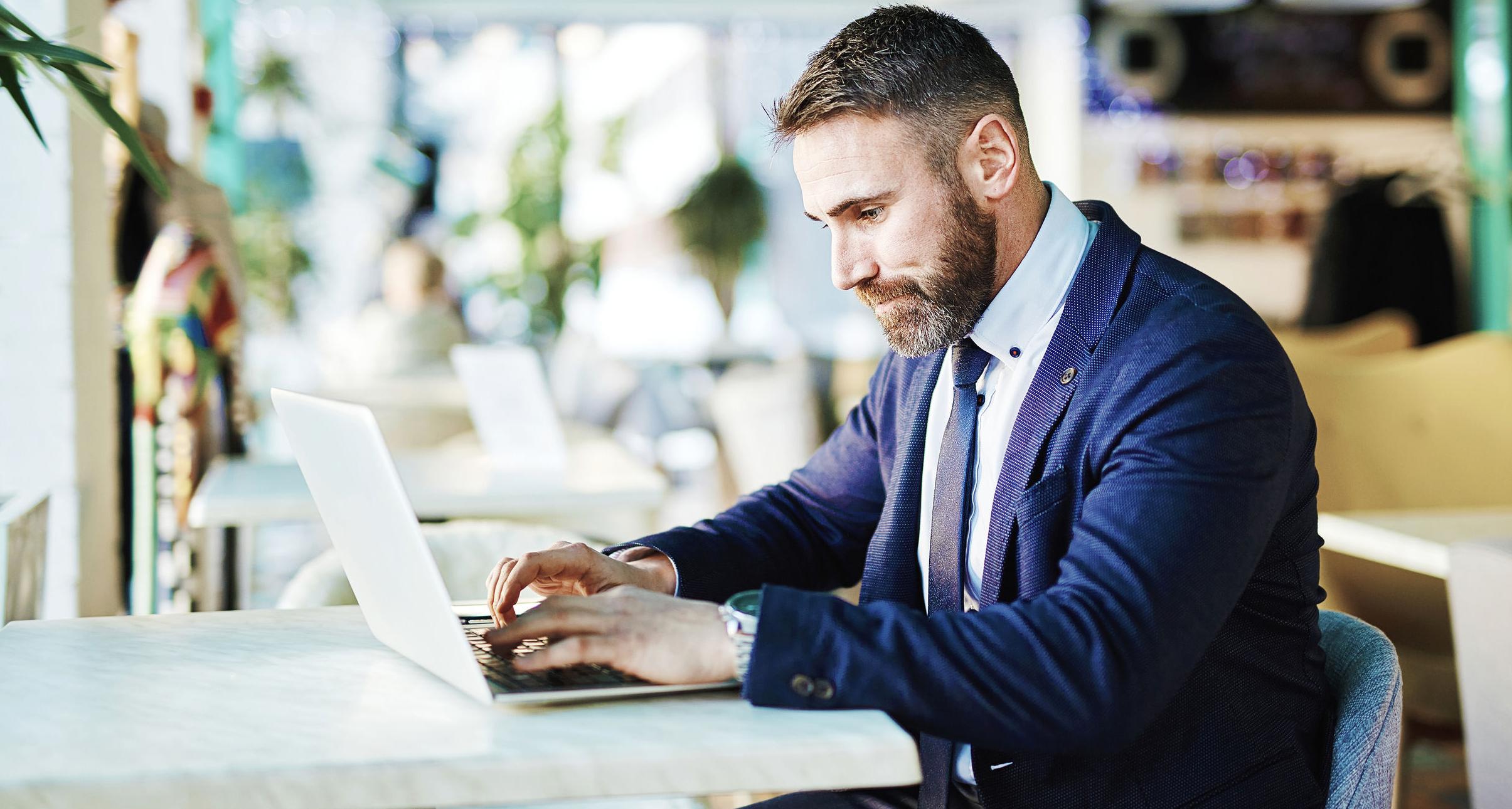 Férfi ül egy kávézóban, és e-mailt ír laptopon.