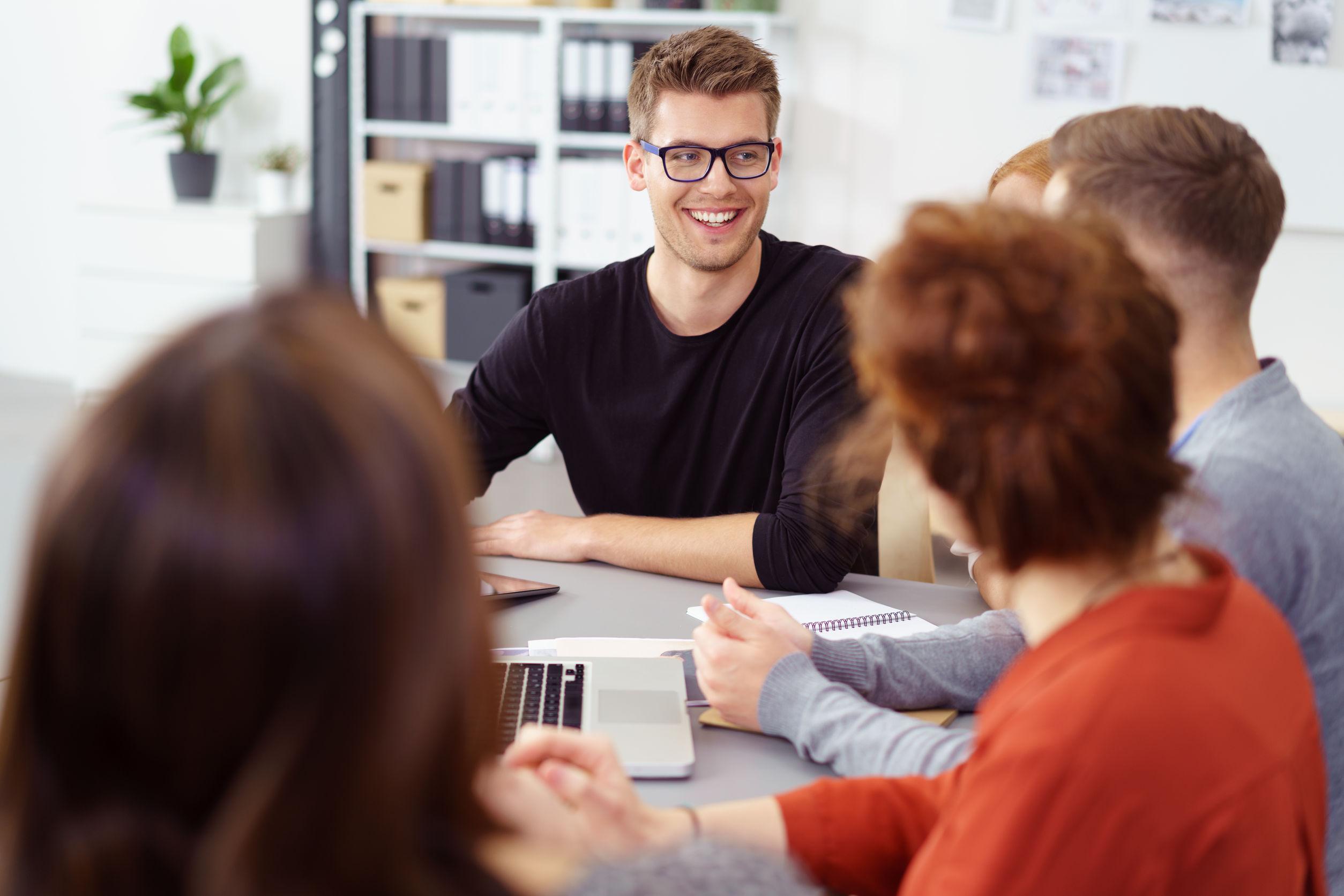 Egy fiatal férfi mosolyog a kollégáira egy irodai megbeszélésen.