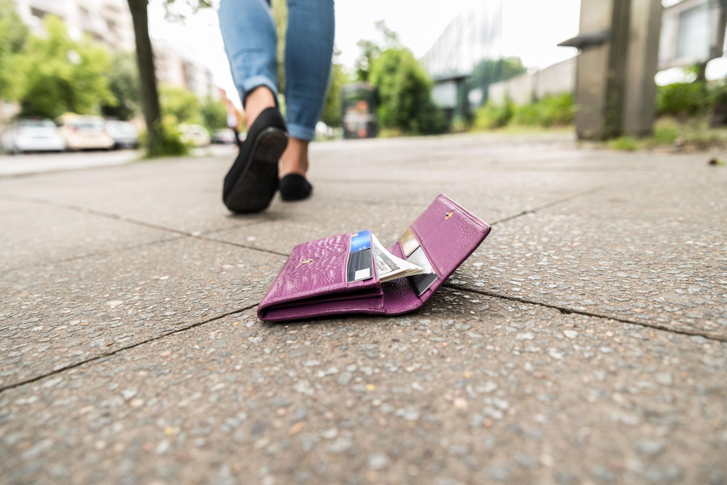 A földön egy lila pénztárca, amit vélhetőleg egy nő ejtett el, akinek a lábai látszanak.