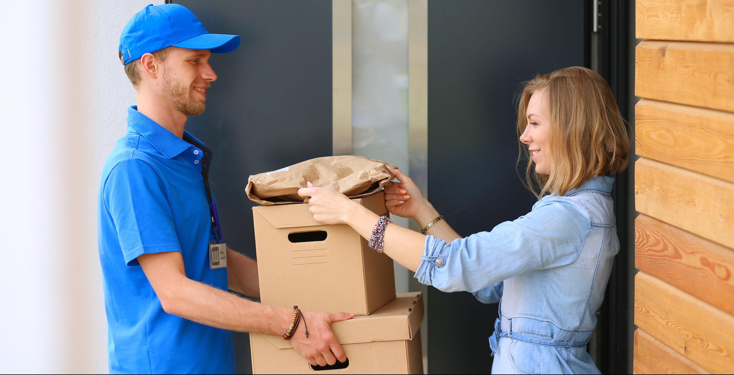 Egy nő világoskék ruhában két papírdobozt vesz át egy kék ruhás postástól.