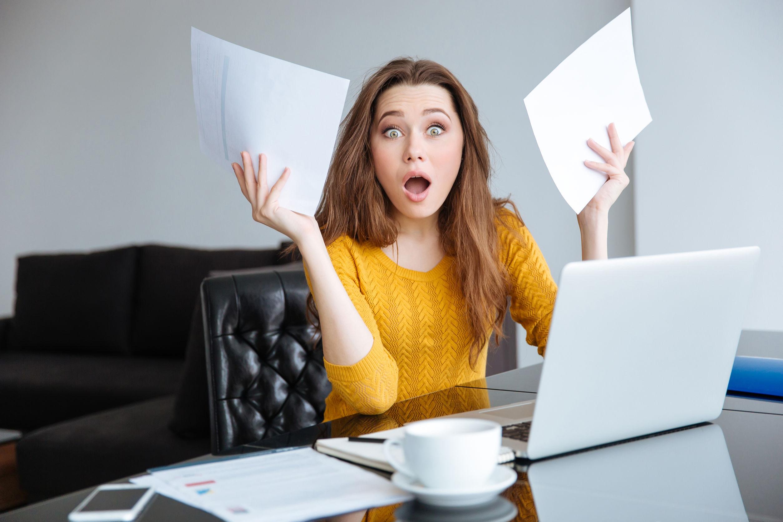Egy nő az asztal és laptop mögött csodálkozva két számlát emel a magasba.