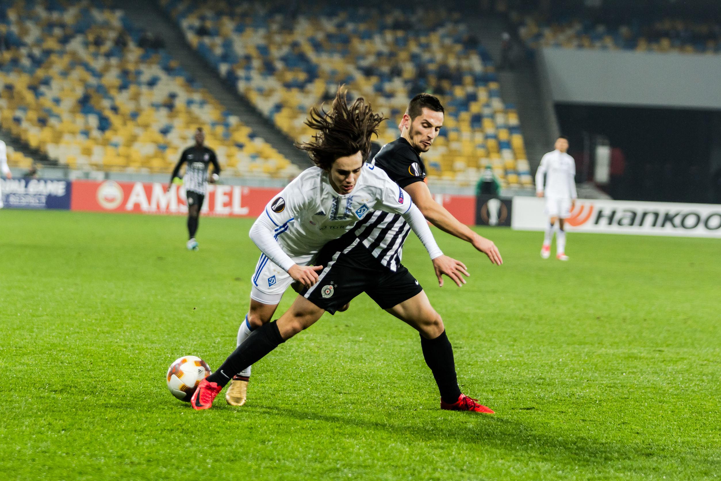 Egy fekete és fehér csíkos focista nyújtott lábbal el gáncsol egy fehér mezes focistát.