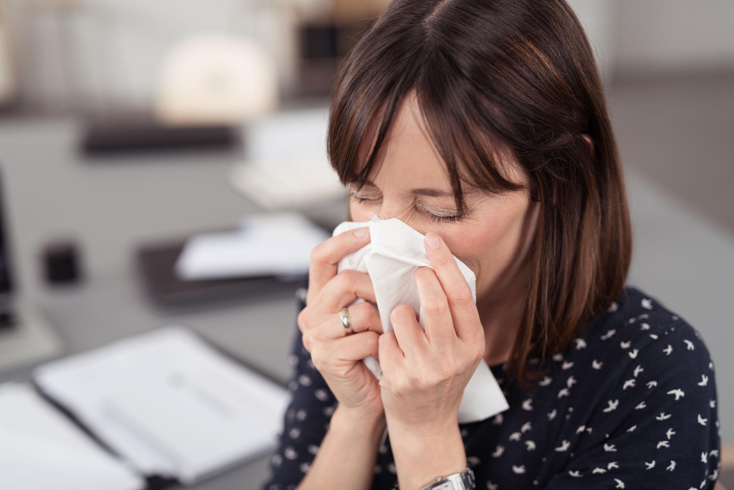 Egy nő az irodában ül betegen, és fújja az orrát.