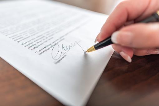 Egy női kéz aláír egy végrendeletet.