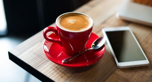 Egy kávézó asztalán van egy kávé, egy telefon és egy laptop.