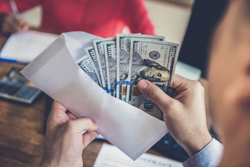 Egy férfi megszámolja a pénzt a borítékban.