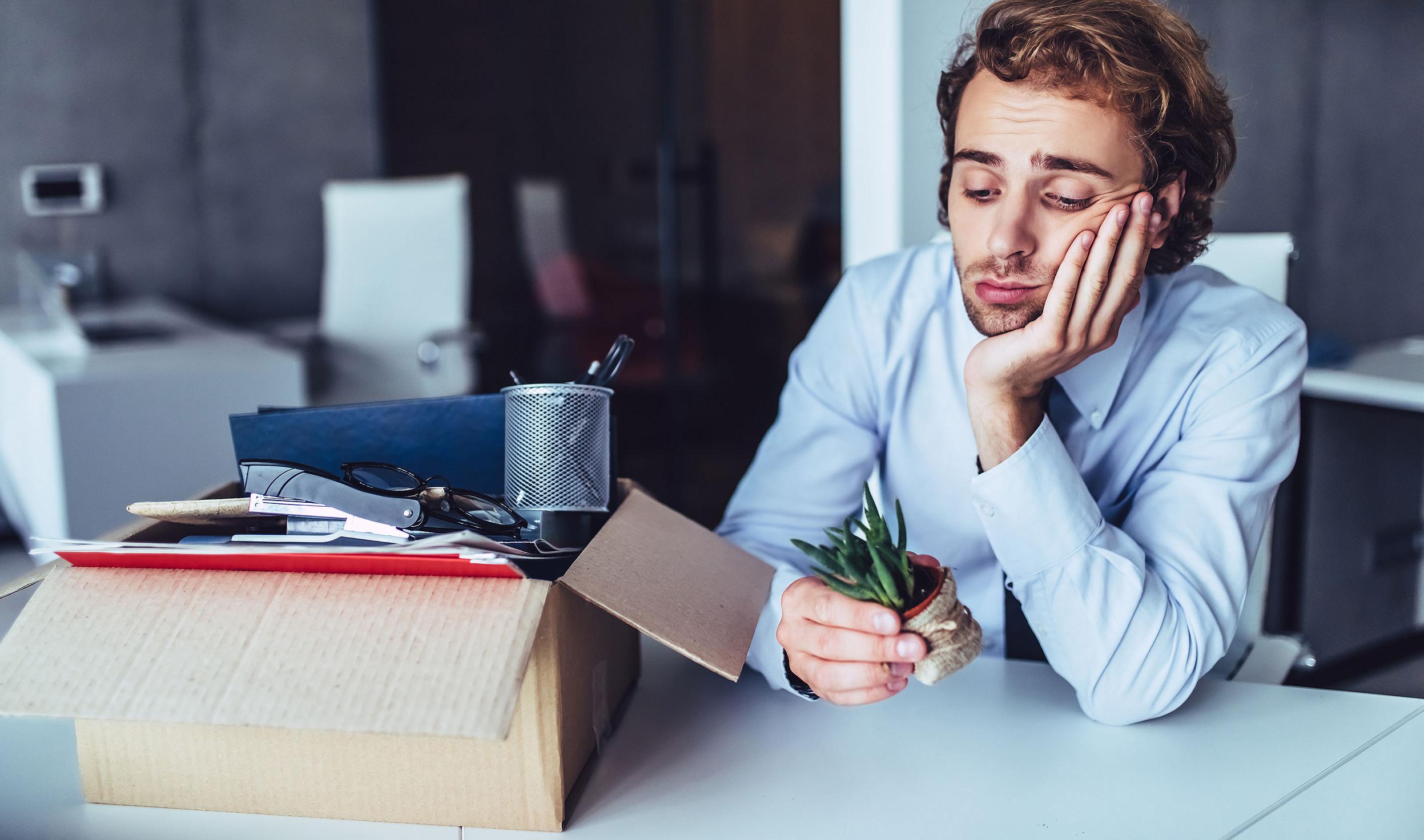 Fiatal üzletember egy dobozba pakolta a dolgait az irodában. Ez az utolsó napja a munkahelyén. Szomorú, mert felmondtak neki.