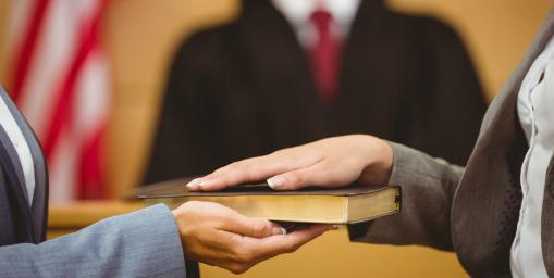 A tanú a bibliára teszi a kezét. Egy másik kéz tartja a bibliát.