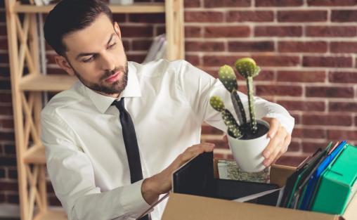Egy fiatal üzletember a dolgait egy dobozba pakolja.