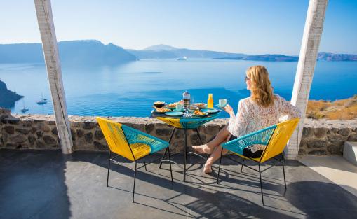 Egy nő a nyaraláson, a teraszon reggelizik