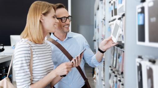 Egy férfi és egy nő telefont vásárol és néz egy boltban.