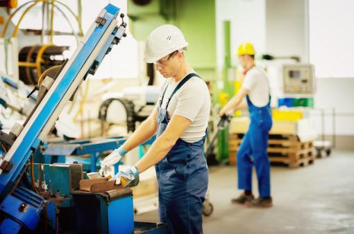 Két munkás férfi a dolgozik a gyárban.