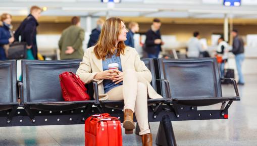 Egy nő a nemzetközi repülőtéren várakozik.