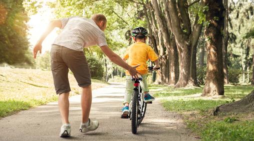 Az apa biciklizni tanítja a fiát