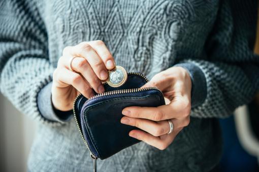 Valaki a kezében fog egy pénztárcát és egy érmét vesz ki belőle.
