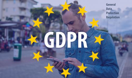 Új Adatvédelmi Rendelet, GDPR szöveg EU zászlóval az előtérben, háttérben egy férfi a mobilját használja.