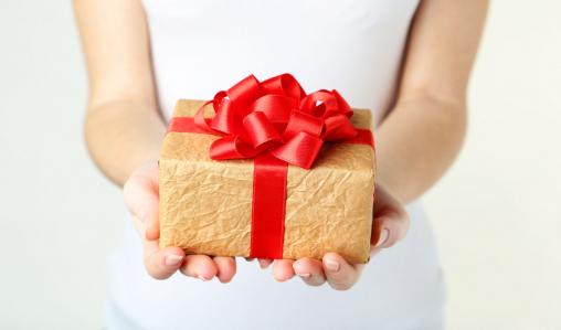 Egy nő ajándékcsomagot tart a kezében.