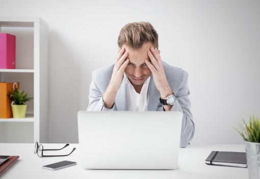 Frusztrált üzletember ül a laptop előtt.