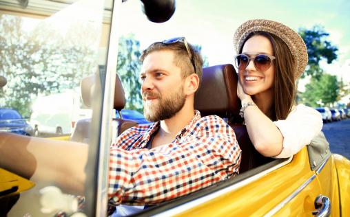 Egy mosolygós fiatal pár ül egy sárga autóban, és nyaralni készülnek. A férfi vezet.