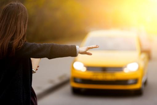 Egy nő taxit hív, a kezével jelez.