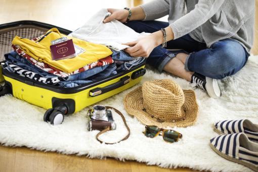 Egy lány nyaralásra készül, és a bőröndjébe csomagol.