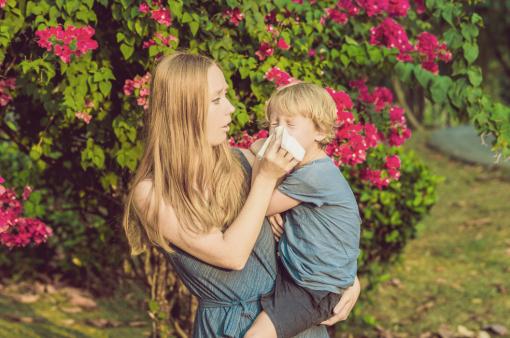 Az anya segít kifújni a gyereke orrát, aki allergiás a parlagfűre.